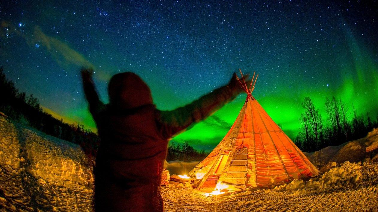 En samisk kåta, den traditionella samiska bostaden, under norrsken.