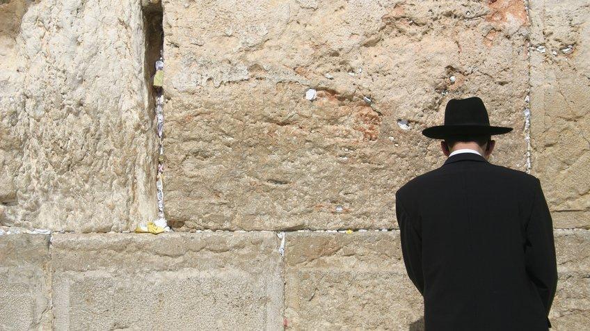 En judisk man ber vid Västra muren. Västra muren är det enda som återstår av judarnas tempel i Jerusalem. Vilka förstörde templet och när?